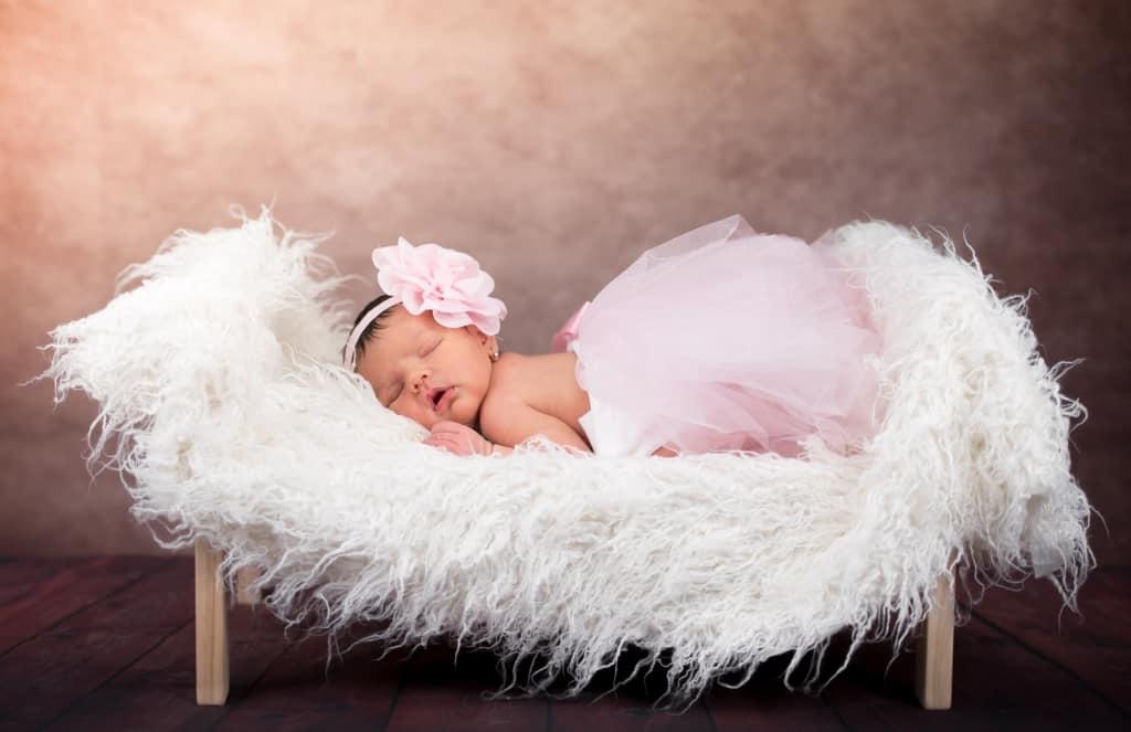 Baby girl sleeps on furry lounge.