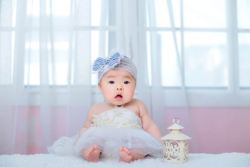 Baby in tutu dress poses for camera.