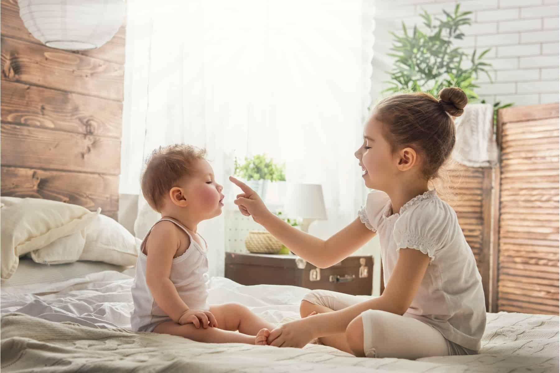 toddler and baby siblings playing together sitting