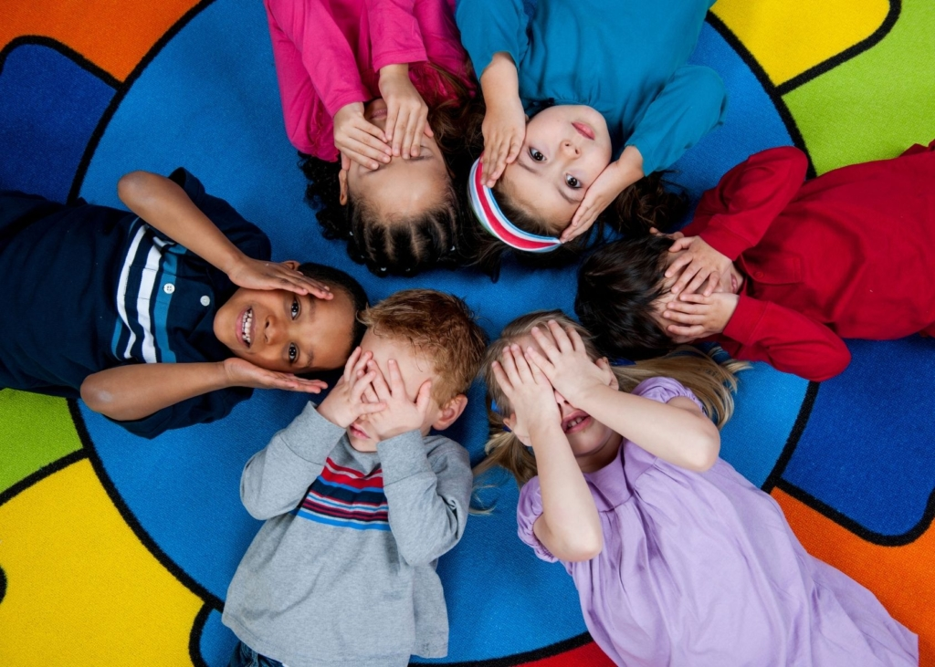 Children play a game and cover their faces in a circle.