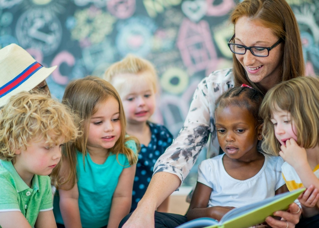 Teach reads to a group of toddlers.