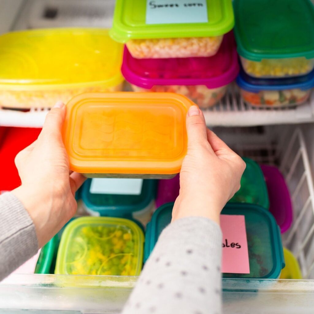 Woman grabbing freezer meal from the freezer.