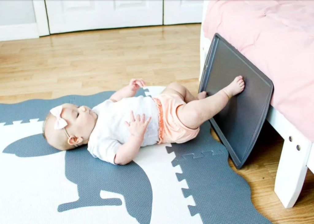 Baby taps feet on cooking sheet for sensory play.