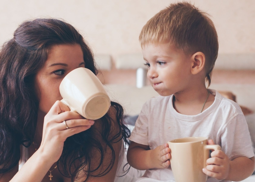 Mom and toddler drink from mugs.