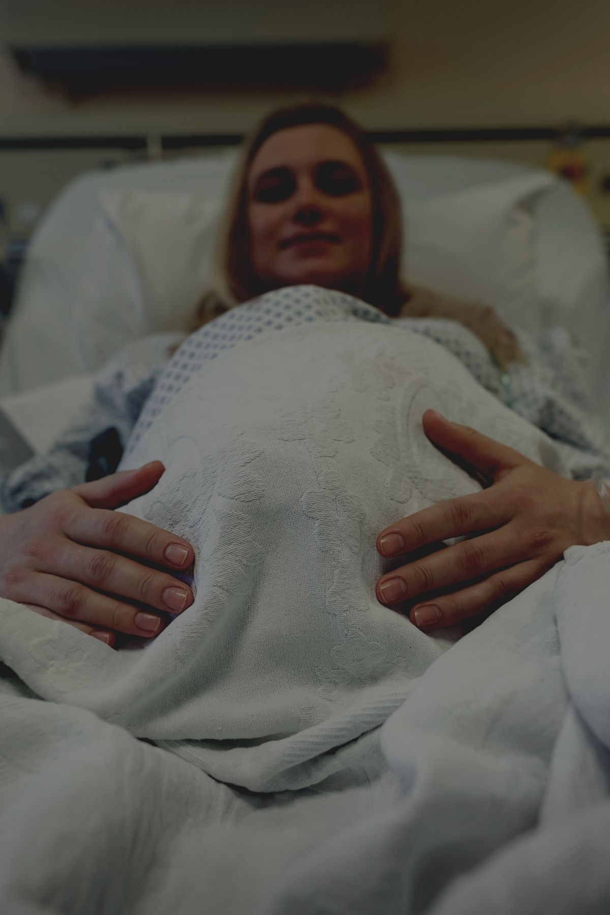 Pregnant woman prepares for birth on hospital bed in dimmed delivery room.