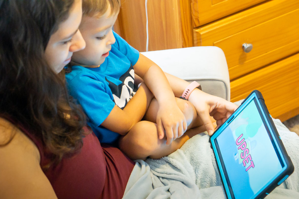 Mom and boy watching a tablet and learning about emotions.
