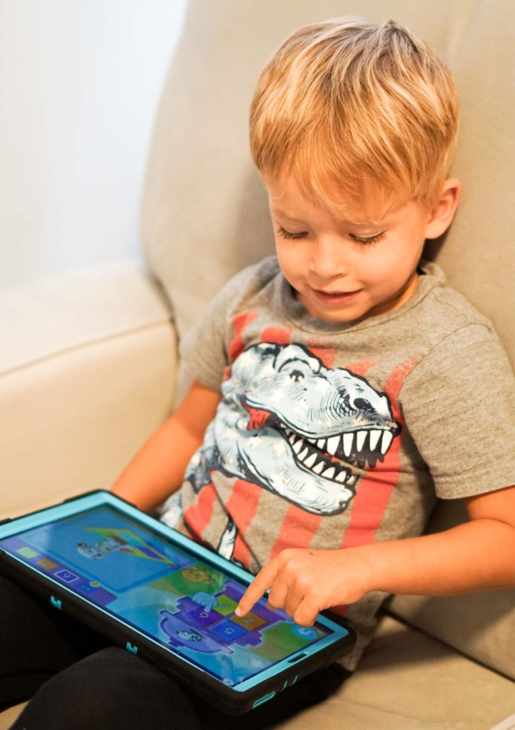 Toddler playing math game on tablet while sitting in an armchair.