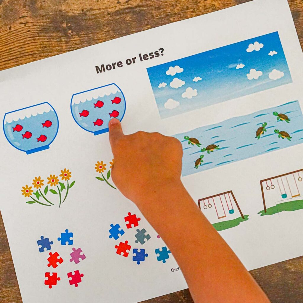 """Toddler pointing at a math worksheet with pictures of items to guess """"more or less?"""""""