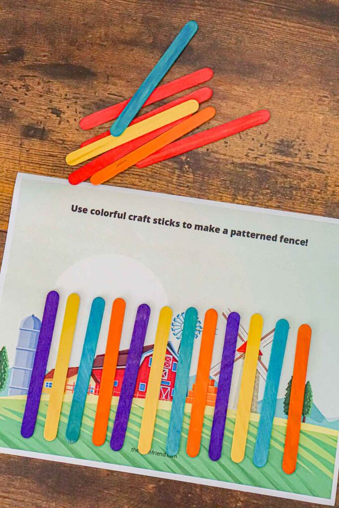 """A """"fence"""" made from craft sticks on a piece of paper with a picture of a barn to teach preschoolers about patterns."""