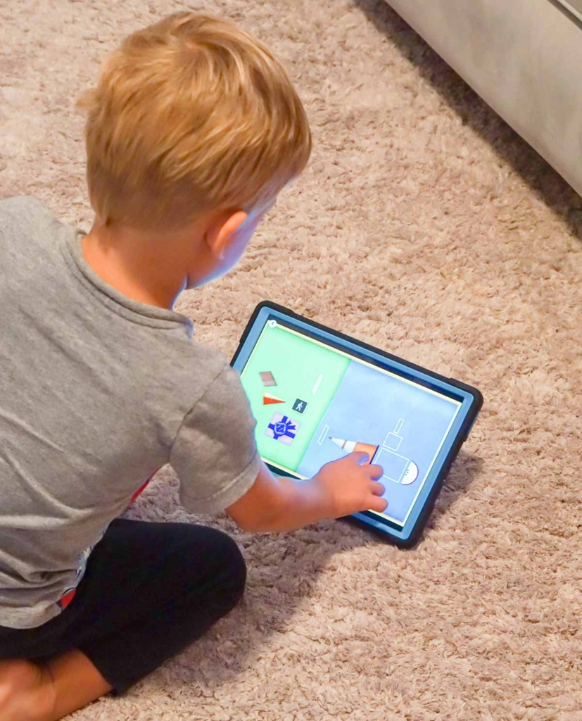 Toddler playing shape game on a tablet.