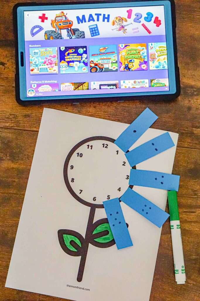 Preschool math activity where you stick on numbers to a paper clock with a tablet in the background.