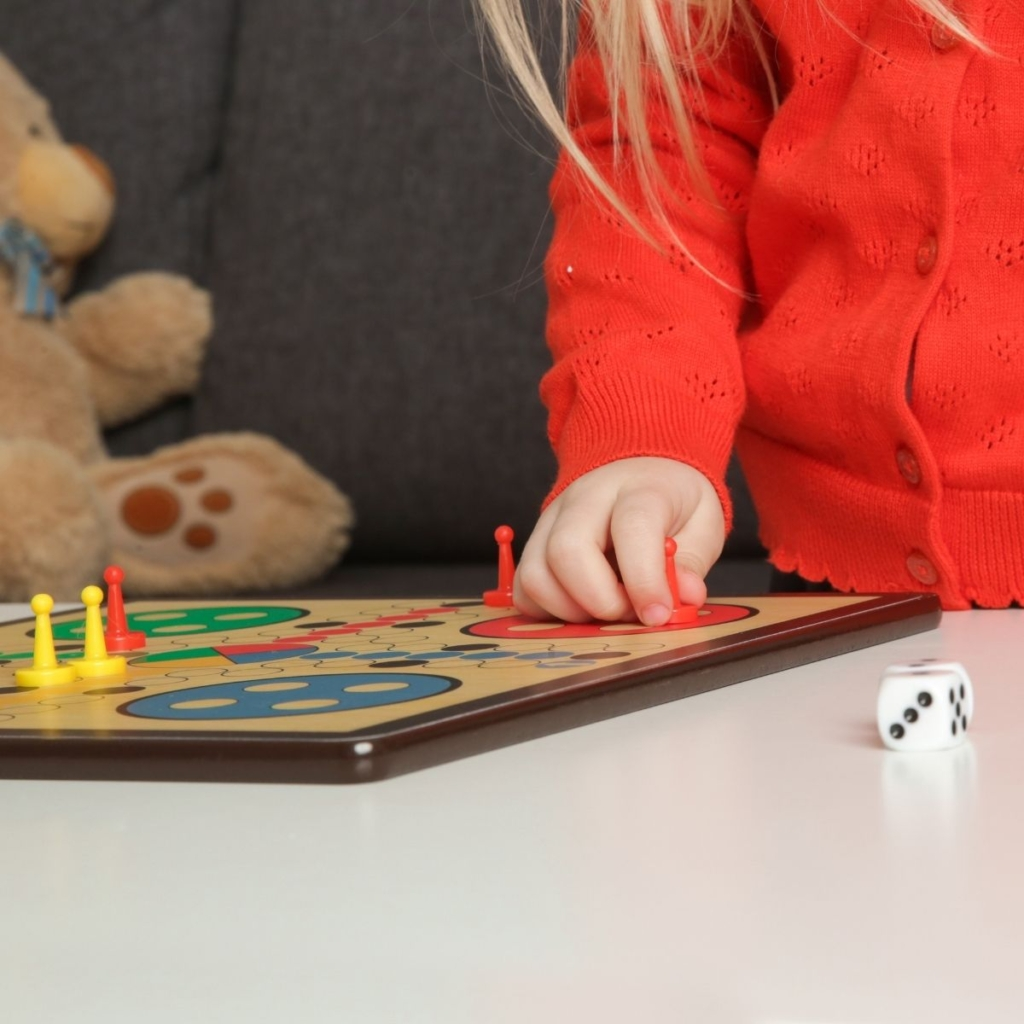 Close up picture of a preschool girl playing a board game.