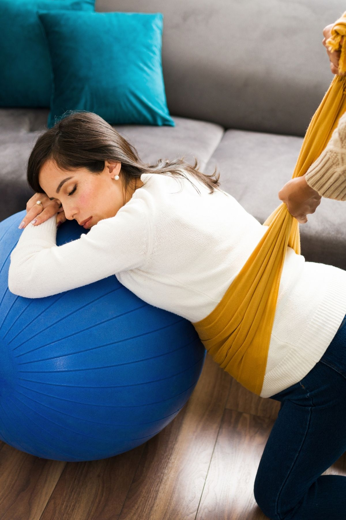 Woman leans over birthing ball while her midwife relieves her stomach pain with rebozo scarf.